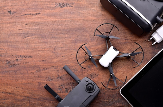 Hobby racing drone concept. drone equipment, remote controller, video receiver, charger, mobile and quadcopter. closeup top view copy space for text.