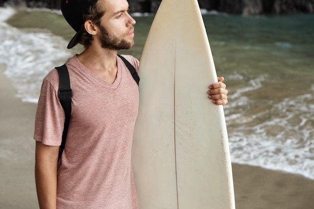 趣味、ウォータースポーツ、アクティブなライフスタイルのコンセプト。野球帽をかぶった若いサーファーが砂浜に一人で立って、思慮深い表情で海を見ている