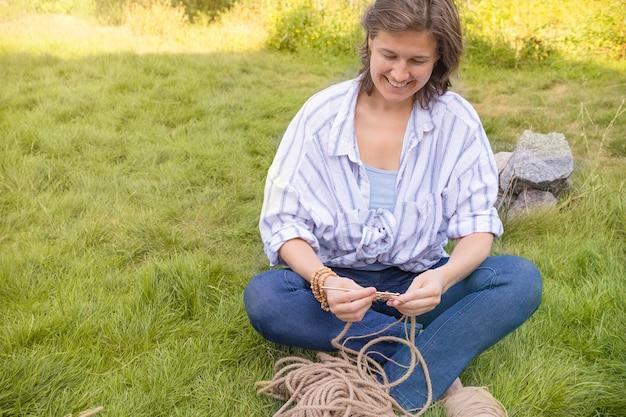 Хобби женщина вяжет корзину из толстого шнура из экологически чистых материалов крючком домашний декор