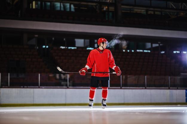 Хоккеист в форме и с клюшкой в руках стоит на льду и готовится атаковать противоположного игрока. интерьер зала.