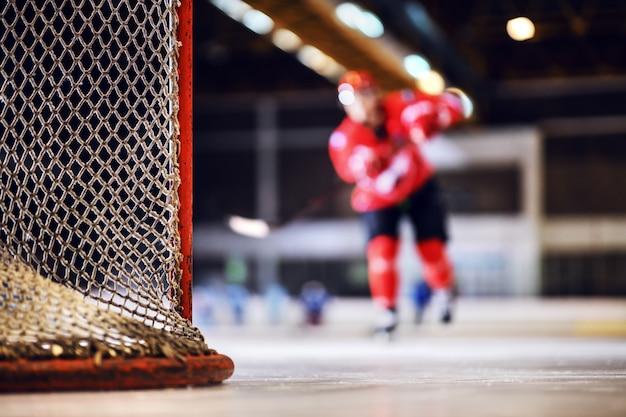 Hockey player skating towards goal and shooting at it.
