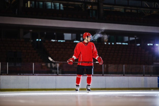Hockey player in uniform and with stick in hands standing on ice and preparing to attack opposite player. hall interior.