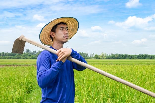 Hoeに立つアジアの農民が希望を持って空を見ています。新鮮な未来を見る