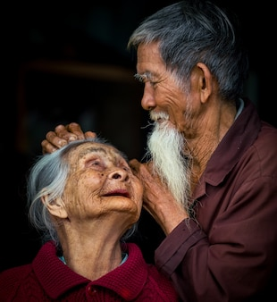Хойан, вьетнам - 14 марта 2018: подробный портрет азиатской пары крупным планом на черном фоне