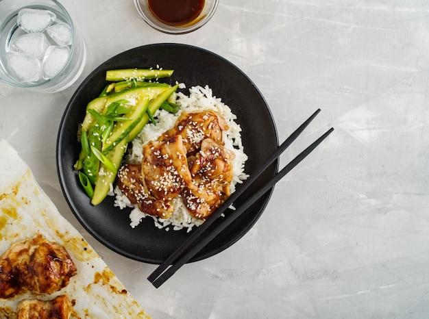 호 이신 치킨. 전통 아시아 요리. 소스, 쌀, 절인 오이를 곁들인 치킨.