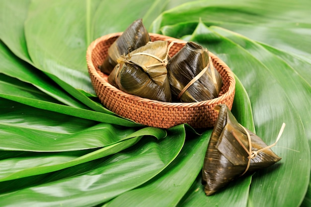 Хоккианские рисовые клецки zongzi, bakcang или bacang. традиционная китайская еда на зеленом бамбуковом фоне фестиваля лодок-драконов, фестиваля дуаньу. концепция дизайна для рекламы.