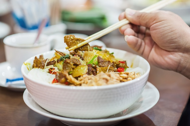 Hold chopsticks of vietnamese grilled pork with rice noodles