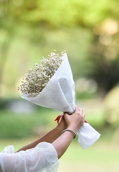 Hold flower bouquet wedding flower in bride hand beautiful to gift woman nature green back