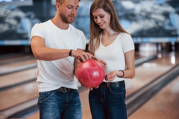 Tienilo in questo modo. uomo che insegna alla ragazza come tiene la palla e gioca a bowling nel club