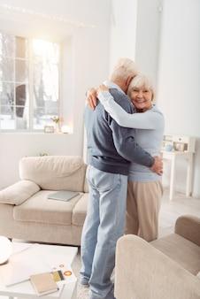 抱きしめて。幸せな年配の女性が夫とダンスをしながら彼をしっかりと抱きしめながらポーズをとって