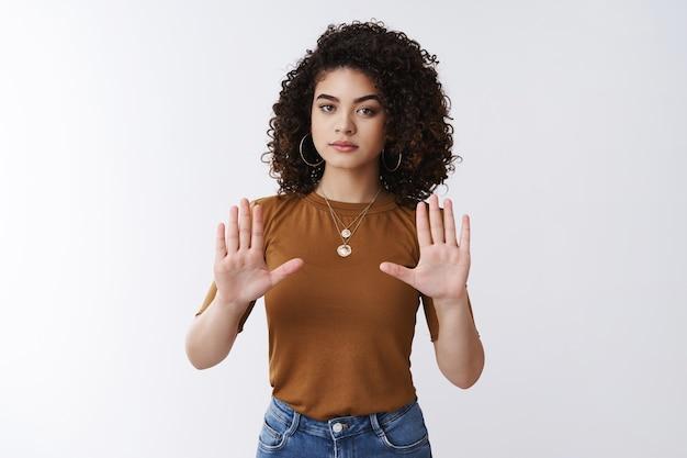 Держись, не подходи. серьезно выглядящая мощная стильная молодая современная женщина-феменистка, вьющиеся, темные волосы, сторонница лгбт, поднимите руки, остановите жест, уверенно откажитесь, откажитесь