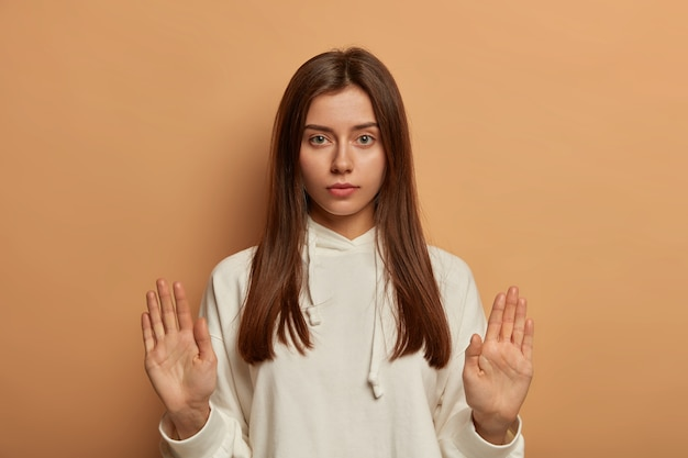 少し待ってください!真面目で落ち着いたヨーロッパの女性が停止ジェスチャーで手のひらを上げ、友人をなだめようとし、招待を断る