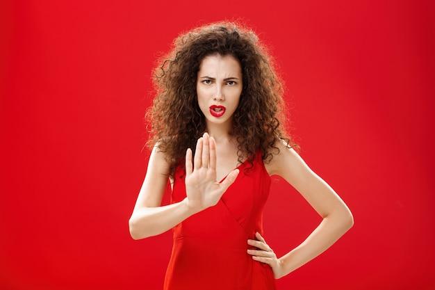 잠깐만요. 강렬한 진지한 표정의 불쾌한 성인 여성은 세련된 빨간 드레스에 곱슬머리를 하고 부정적인 대답을 거부하고 가까이 오는 것을 금지하는 제스처로 손바닥을 들어올립니다.