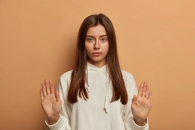 Attendere prego! la donna europea seria e calma alza i palmi in segno di arresto, cerca di calmare l'amico, rifiuta l'invito