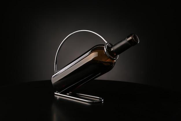 Holder with bottle of wine on dark