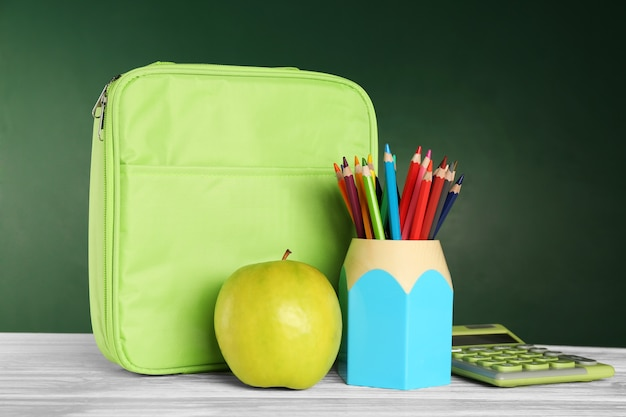 Holder with colorful pencils, lunch bag and appetizing green apple on wooden table against blackboard wall