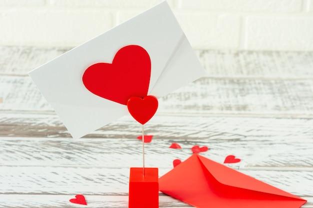 ラブレター付き封筒付きホルダー。木製の背景に聖バレンタインデーのポストカード。紙のハートが付いたお祝いのグリーティングカード。
