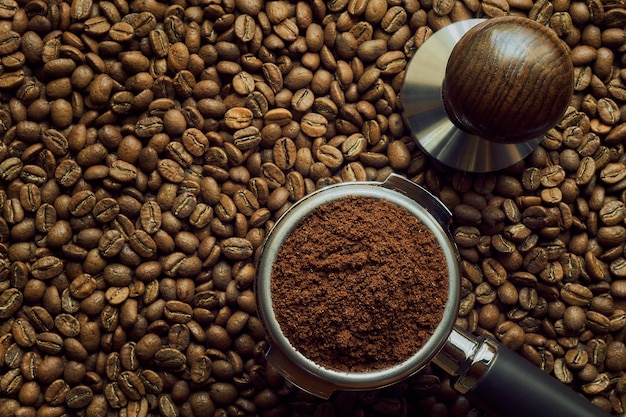 Holder with freshly ground coffee lies on a background of freshly roasted coffee beans, with copy space