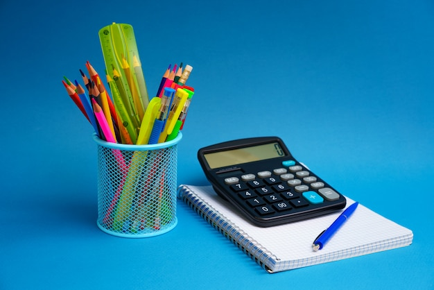 Holder with pens and pencils and  notebook with a calculator on a blue background. back to school concept. horizontal photo copy space