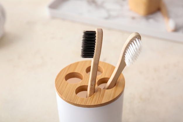 Holder with wooden toothbrushes on table in bathroom