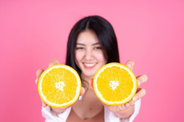 Красота женщина азиатская милая девушка чувствовать себя счастливым holdind оранжевый плод для хорошего здоровья на розовом фоне