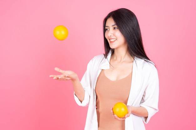 美しさの女性アジアのかわいい女の子はピンクの背景に健康のため幸せholdindオレンジ色の果物を感じる