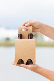 Holding 4 pack of beers to celebrate on the beach