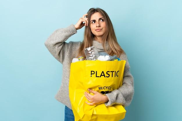 Держа мешок, полный пластиковых бутылок, чтобы перерабатывать на изолированных синий с сомнением и с запутанным выражением лица