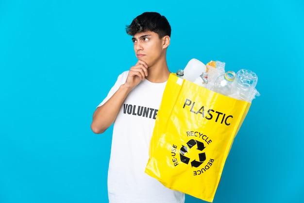 파란색 배경 위에 재활용 플라스틱 병으로 가득 찬 가방을 들고 찾고