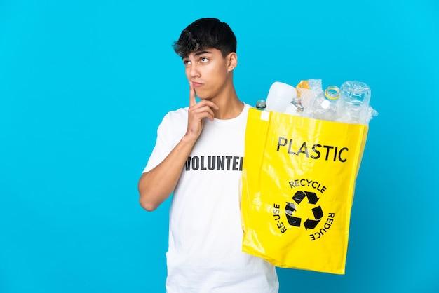 찾고있는 동안 의심을 갖는 파란색 배경 위에 재활용 플라스틱 병으로 가득 찬 가방을 들고