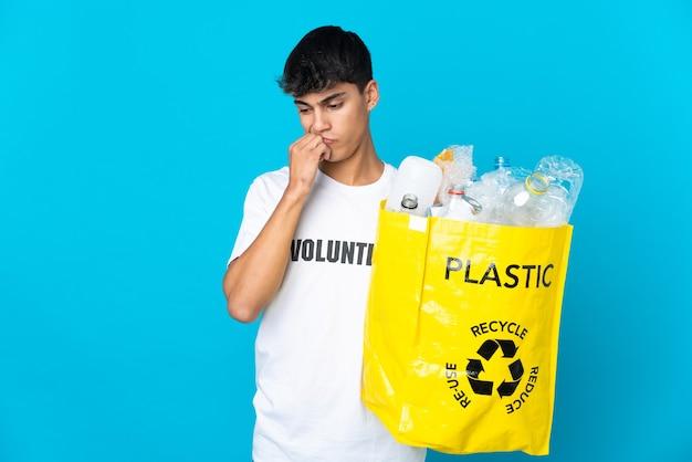 Держа мешок, полный пластиковых бутылок для переработки на синем фоне, сомневаясь