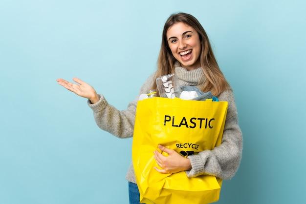 Держа мешок, полный пластиковых бутылок для переработки, над изолированными синими руками, вытягивая руки в стороны, приглашая прийти