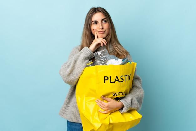 アイデアを考えて孤立した青をリサイクルするためにペットボトルがいっぱい入った袋を握る