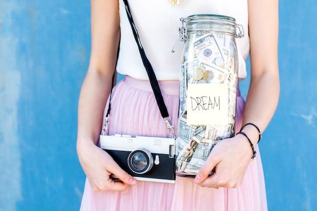 파란색 배경에 사진 카메라가 있는 꿈을 위해 저축한 병을 들고 있습니다. 사진작가를 꿈꾸며