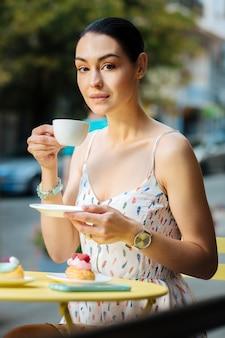 カップを持っています。素敵なカフェのテラスで午後を過ごしながらコーヒーを楽しんでいる美しい穏やかな女性