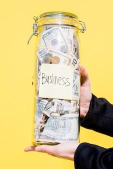 Держа стеклянную бутылку, полную сбережений денег для инвестиций в бизнес на желтом фоне