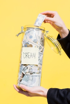 Держа стеклянную бутылку, полную сбережений денег для мечты на желтом фоне