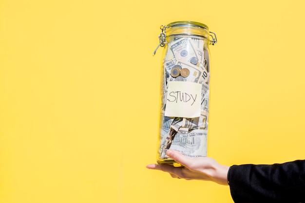 Держа стеклянную бутылку, полную сбережений денег для исследования на желтом фоне
