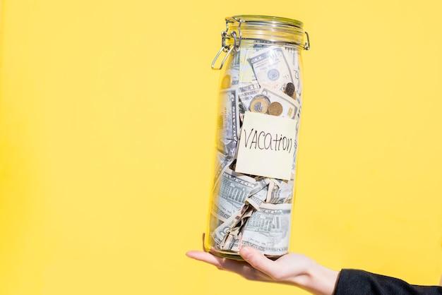 Держа стеклянную бутылку, полную сбережений денег на летние каникулы на желтом фоне