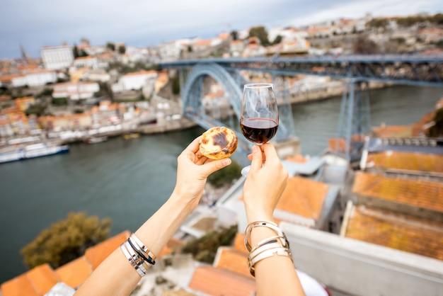 ポルト、ポルトガルの美しい街並みの背景にパステルデナタと呼ばれる伝統的なポルトガルのデザートと赤ワインのグラスを保持します。