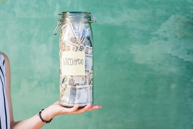 緑の背景にステッカーでお金でいっぱいの瓶を保持します。旅行のコンセプトのためのお金の節約