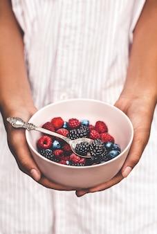 Держит тарелку с ягодами. смесь для завтрака. малина, черника, ежевика. пластина