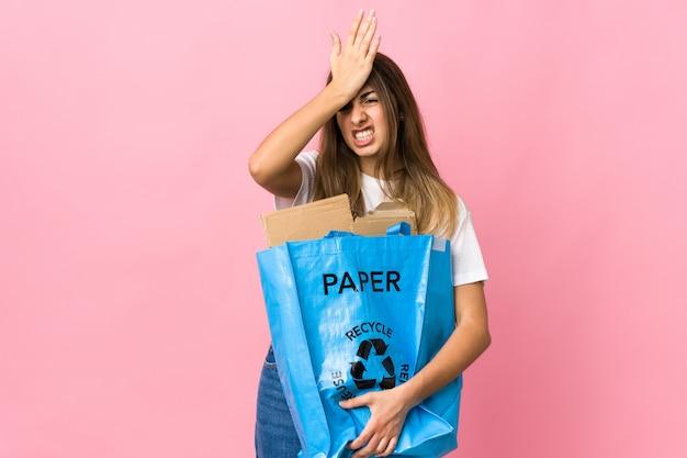 Держа мешок рециркуляции, полный бумаги, чтобы перерабатывать на изолированном розовом, имея сомнения с путать выражение лица