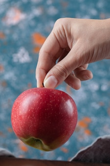 Держа красное яблоко в руке на синей поверхности