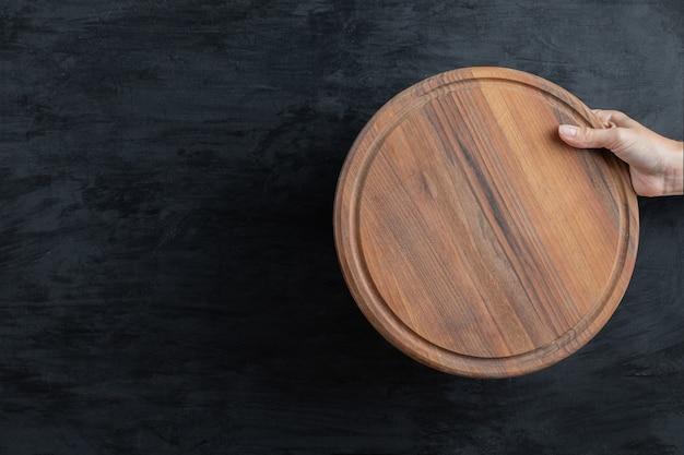 手に丸い木製の大皿を持って