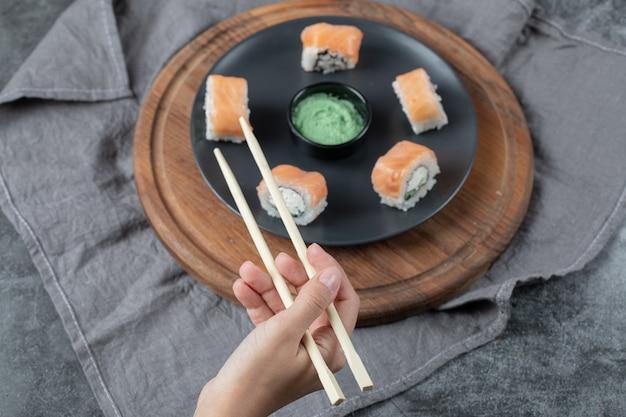 젓가락으로 연어 초밥 롤을 들고.