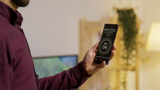 画面にスマートライトアプリを搭載したスマートフォンを持ち、家の中でライトをオンにする