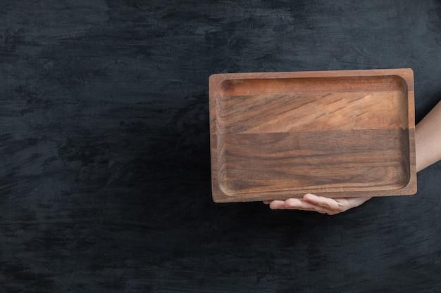 手に正方形の木製の大皿を持って