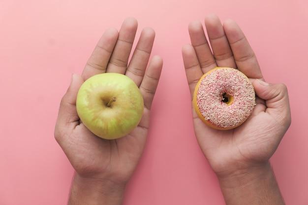 リンゴの果実とドーナツを保持し、健康食品の概念を選択します