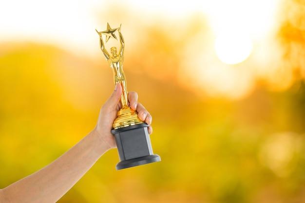 Держит трофей для церемонии награждения победителей шоу.